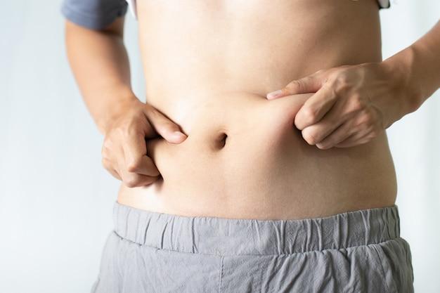 Молодой человек, касаясь его толстый живот. концепция жира и здоровья