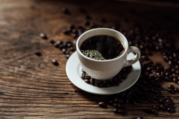 Чашка горячего черного кофе и кофейных зерен на деревянный стол с естественным освещением по утрам