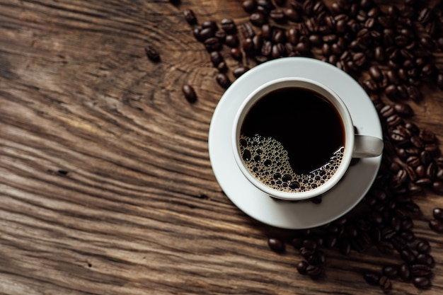 熱いブラックコーヒーカップと朝の自然光と木製のテーブルの上のコーヒー豆