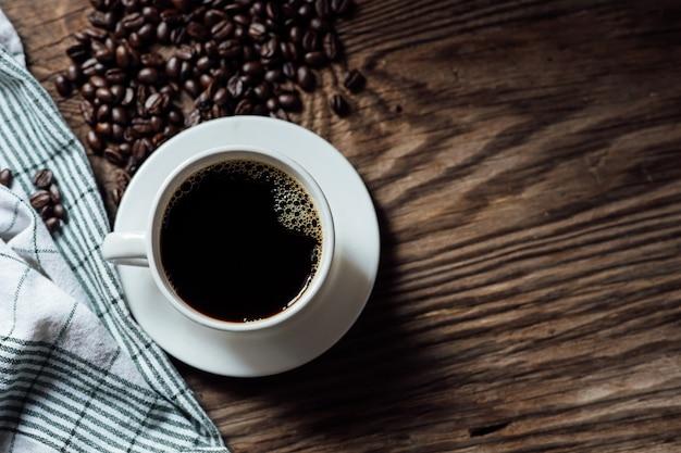 Горячая черная кофейная чашка и кофейные зерна на деревянном столе с естественным светом в утре. кофейная чашка сверху