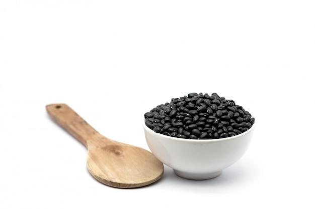 ボウルと分離された木のスプーンで自然な黒豆。ビタミンと鉄分の栄養素を提供する黒豆。