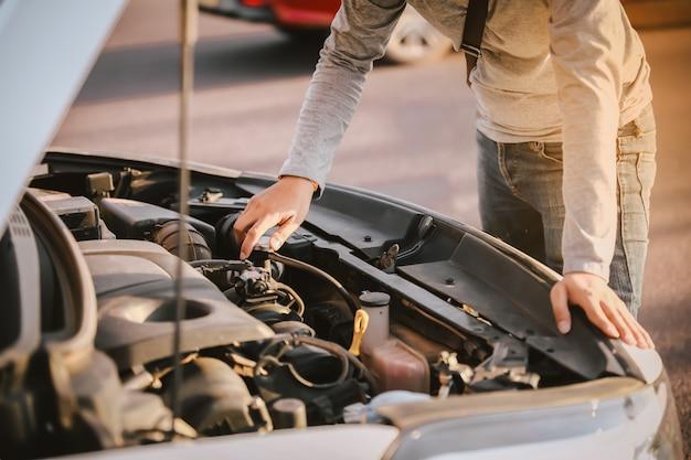 若い男が彼の壊れた車の前に立って、エンジンをチェックするためのフードを開けた