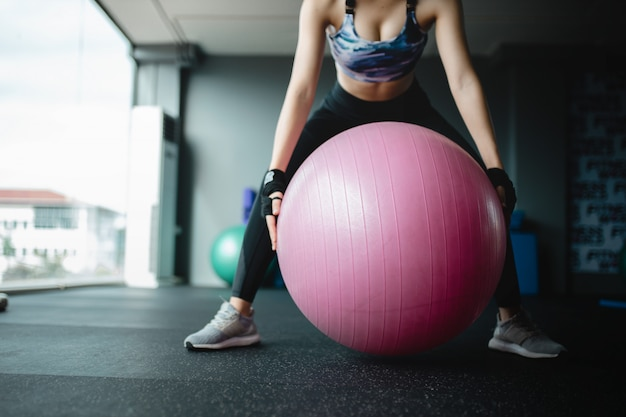 Конец вверх по азиатской модели женщин держит шарик йоги на спортзале подготавливая для тренировки, девушка тренировки