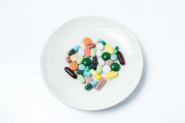 カラフルなカプセルと白い皿の上の丸薬。健康