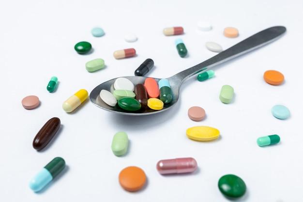 カラフルなカプセルとスプーンの丸薬。健康