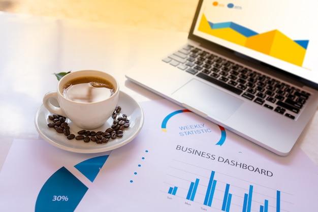 Кофейная чашка и кофейные зерна на белом столе в офисе с документами рабочих процессов, компьютер ноутбук