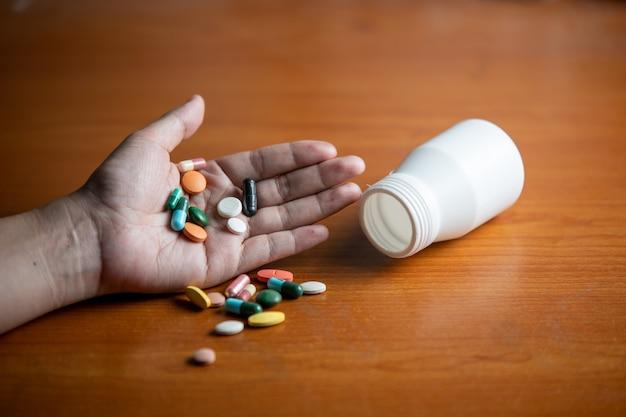 Таблетки и капсулы на руках у женщин