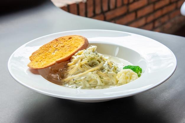 Спагетти карбонара с багетом на белой тарелке