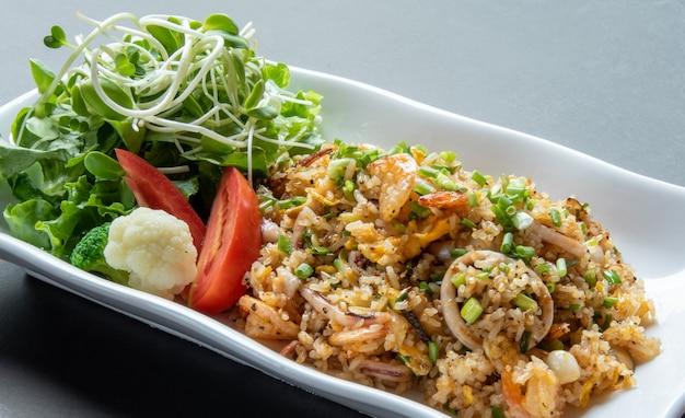 Вкусные жареные рисовые морепродукты на современной белой тарелке