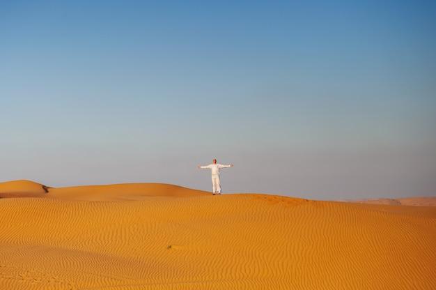 Портрет испытывающего жажду арабского человека на середине желтой пустыни.