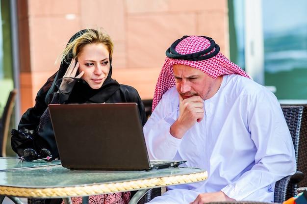 Коммерсантка или продавщица работая с арабским человеком показывая продукты в таблетке в кофейне