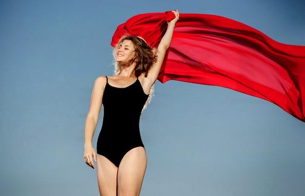 夕焼け空と赤い布の前でポーズをとってプロの体操選手ダンサー
