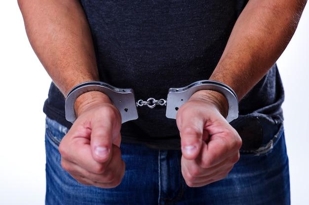 警察のスチール製の手錠が犯罪の人間の手を逮捕します。