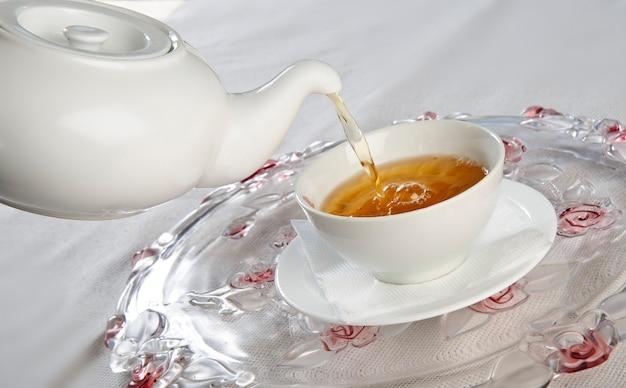Чайник и чашка для чая, на белой предпосылке.