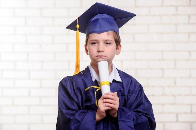 カップとガウンの卒業証書でポーズの小学生少年。