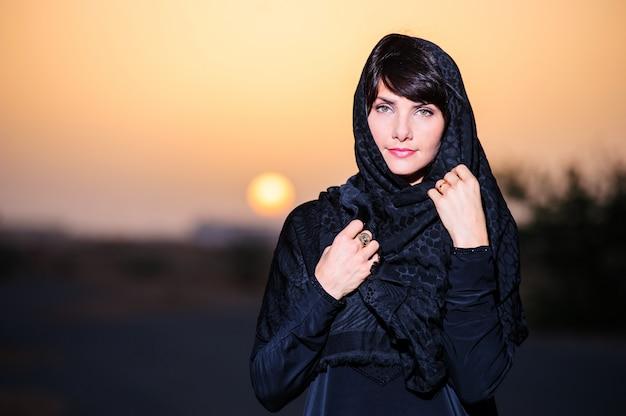 女性は夕日を背景に中東のウェイポーズを着ています。
