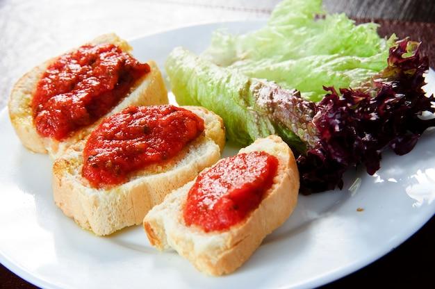 Канапе или кростини на грифельную доску. идеально в качестве аперитива. состав: поджаренный багет с семенами подсолнечника и льна, луковым джемом, сливочным сыром и свежим тимьяном