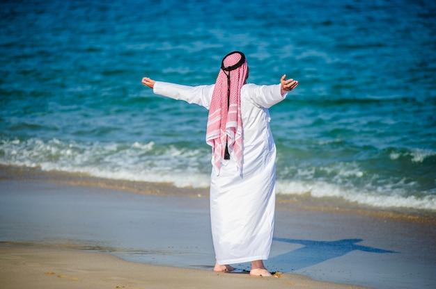 Ближневосточным образом одетый арабский мужчина позирует на берегу моря.