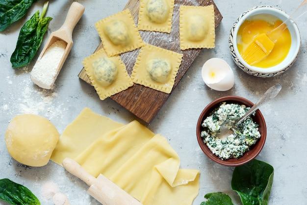青色の背景、伝統的なイタリア料理、トップビューでリコッタとほうれん草のラビオリ自家製パスタを調理
