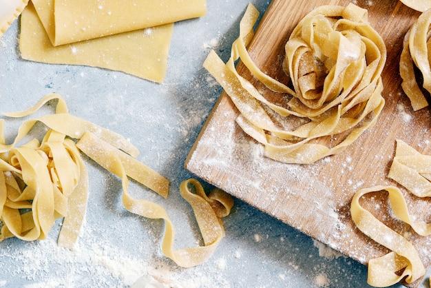 自家製のイタリアのパスタ、ラビオリ、フェットチーネ、タリアテッレ、木の板と青色の背景に。調理プロセス、生パスタ