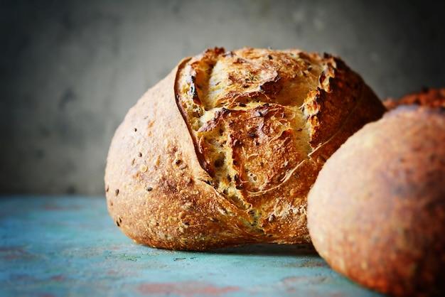 Домашний свежеиспеченный деревенский хлеб из пшеничной и цельнозерновой муки на серо-синем фоне