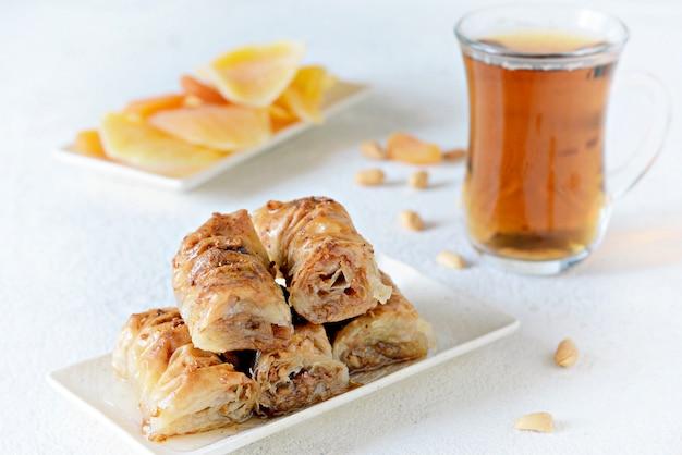 Турецкий десерт из пахлавы с грецким орехом, арахисом, медовым сиропом с черным чаем и сухофруктами, курагой и манго. ближневосточные или арабские блюда. традиционный арабский десерт