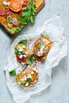 新鮮なトマト、リコッタ、ハーブ、玉ねぎ、オリーブオイル、ルッコラとイタリアのブルスケッタ(サンドイッチ、クロスティーニ、タパス、トースト)は、青色の背景に残します。伝統的なイタリアの前菜またはスナック、前菜