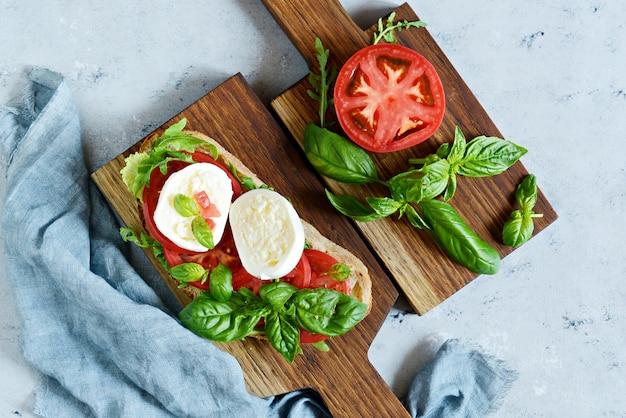 青色の背景に木の板にカプレーゼサラダとイタリアの前菜ブルスケッタ(トースト)、イタリアのパニーニビュー-新鮮な食材をクローズアップ。