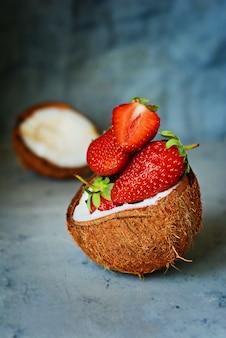 青い(灰色)の壁にココナッツの半分で熟した新鮮なイチゴ。スーパーフード、健康的な朝食、おいしい生のデザート。健康食品のコンセプト、ビーガンフード。