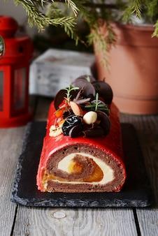 チョコレートユールは、木製の背景にクリスマスケーキをログに記録します。
