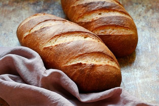 茶色の壁に新鮮なパン。伝統的な小麦の素朴な焼きたてのパン、パンの塊。