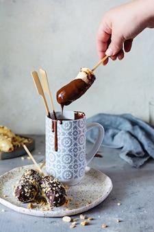 Замороженный банан на палочке, покрытой темным шоколадом и крошкой орехов.