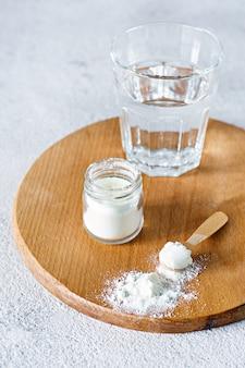 Коллагеновый порошок со стаканом воды на светлом фоне. дополнительное потребление белка. натуральная косметическая добавка для кожи, костей, суставов и кишечника.