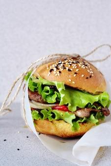 ジューシーなカツレツ、グリルペッパー、オニオン、サラダが入った、フレッシュでおいしいハンバーガー(ハンバーガー)