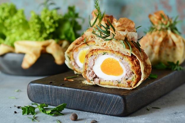 緑のパンケーキバッグにスコッチエッグ。型破りなサービングの古典的な料理。イギリス料理のおいしくて食欲をそそる料理。