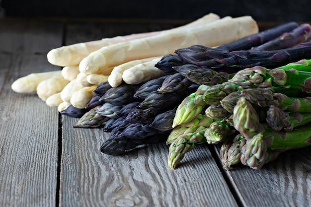 Зеленая, фиолетовая и белая спаржа на темном деревянном фоне