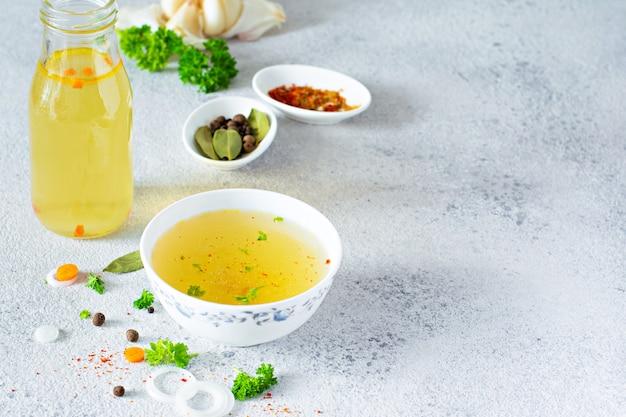 Домашний суп с курицей, овощами, специями и зеленью в миске