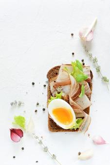 Тост из ржаного хлеба с кусочками бекона, яйцом всмятку и специями