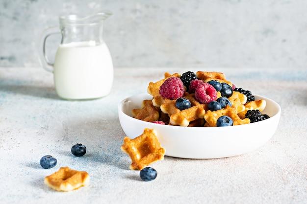 Крошечные (мини) вафли с молоком вафли на завтрак с ягодами в белой миске на белом