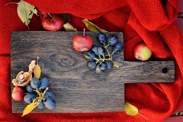 Осенние сезонные пищевые ингредиенты. плоды на разделочной деревянной доске. осенние падающие листья и фрукты на темной деревянной доске. скопируйте место для текста. концепция дня благодарения. концепция урожая фона