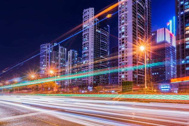 Ночная точка зрения городской дороги и нечетких автомобильных фар