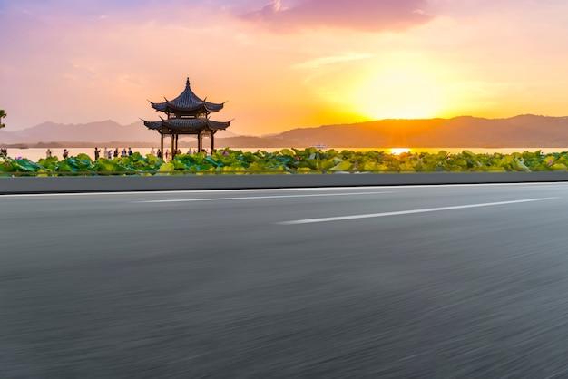 Пустая асфальтовая дорога и природный ландшафт на закате