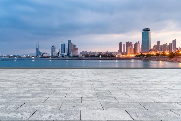 空の大理石の床と青島の都会のビルのスカイライン。