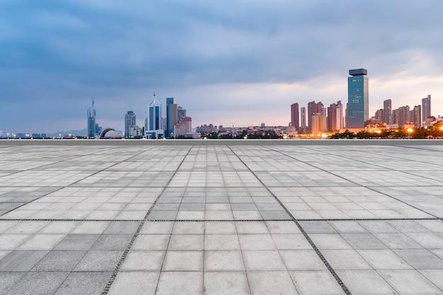空の正方形の床タイルと青島市の高層ビル