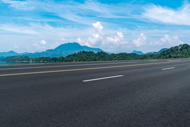 Пустая асфальтовая дорога и природный ландшафт под голубым небом