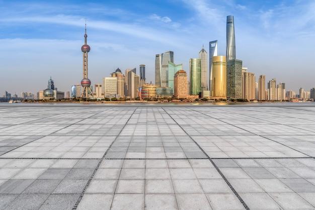 空の正方形の床タイルと都市の高層ビル