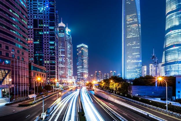 夜の上海市の建物とぼやけた車のライト