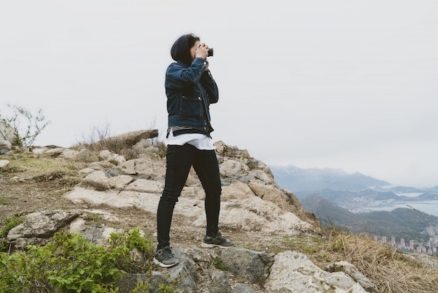 山の頂上で写真を撮る女性