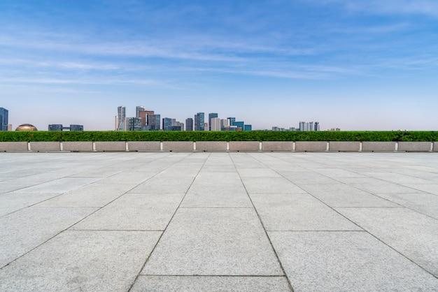 Пустые квадратные плитки и горизонт городских зданий