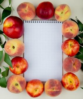 コピースペースを持つ葉で飾られた白い表面上のメモ帳の周りの桃のトップビュー